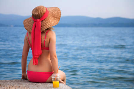 Attractive woman in hat on a seacoast
