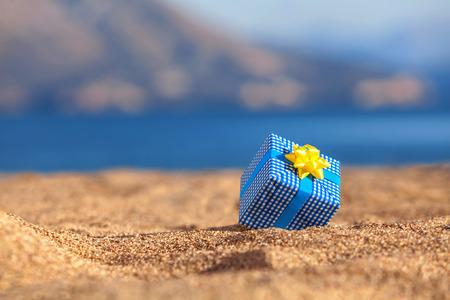 Blauwe geschenkdoos op een strand