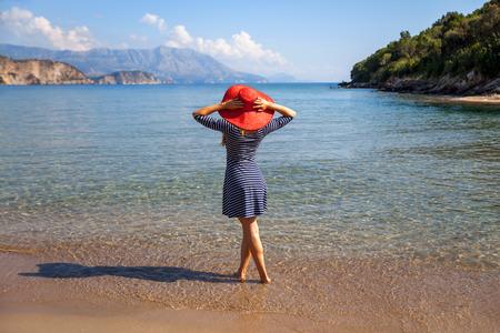 Femme au chapeau rouge debout sur une plage de sable