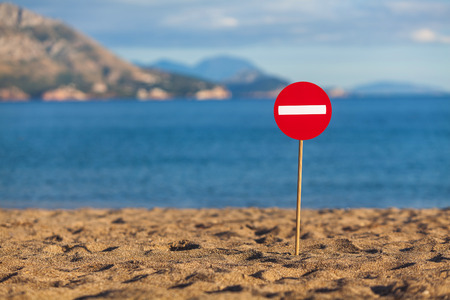 A road sign installed on a sandy beach
