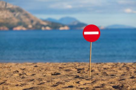 Ein Schild an einem Sandstrand installiert