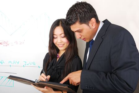 Young beautiful woman and man discussing something near whiteboard
