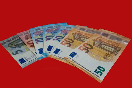euro banknotes on a red background