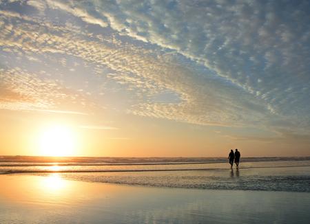 Senior couple walking on  beach at sunrise,  beautiful cloudy sky  and sun reflected on the beach, Jacksonville, Florida, USA.