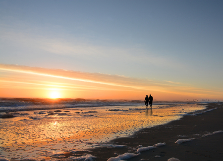 Senior couple holding hands walking on  beach at sunrise, sun reflected on the beach, Jacksonville, Florida, USA.