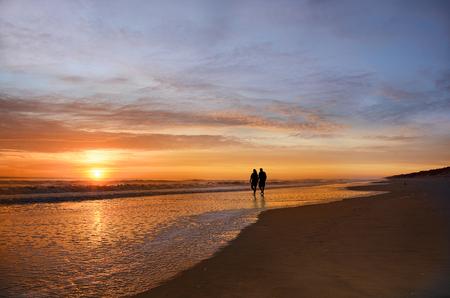 Senior couple holding hands walking on beach enjoying sunrise, sun reflected on the beach, Jacksonville, Florida, USA. Stock Photo