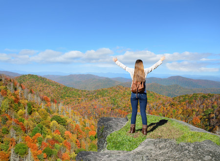 Girl stands on a top of the mountain with her hands up looking at beautiful autumnmountain landscape during his hiking trip. .Copy Space. Near Asheville, Blue Ridge Mountains, North carolina, USA.