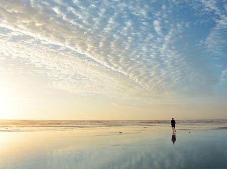 男は日の出では、ビーチの上を歩いてビーチ、ジャクソンビル、フロリダ州、アメリカ合衆国に映る美しい曇り空。 写真素材