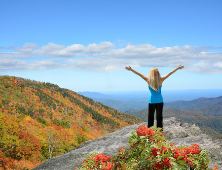 Girl stands on a top of the mountain with her hands up looking at beautiful autumn mountain landscape on  his fall hiking trip. .Copy Space. Near Asheville, Blue Ridge Mountains, North carolina, USA.