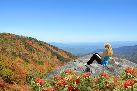 Young woman siting and relaxing on the top of the mountain. Copy Space. Near Asheville, Blue Ridge Mountains, North carolina, USA.