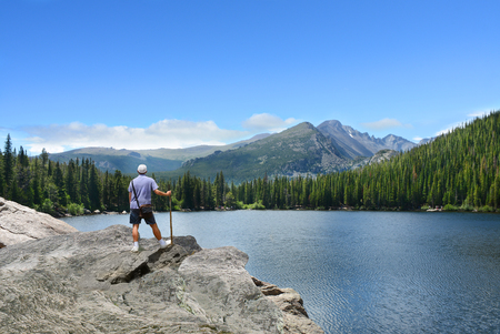 Summer hiking trip. Man standing on the top of the mountain looking at beautiful mountains view. Rocky Mountains National Park, Bear Lake, Colorado.USA.