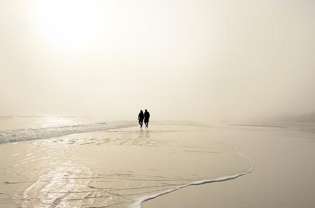 Senior couple holding hands walking on beautiful foggy beach at sunrise. Sun reflected on the beach. Daytona Beach, Florida, USA. Stok Fotoğraf