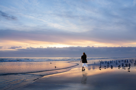 Girl walking on the beautiful beach at sunrise, sun and clouds reflected in the water on the beach, Daytona, Florida, USA. Stok Fotoğraf