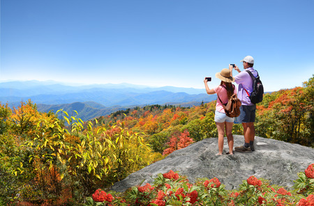 Family hiking in autumn mountains enjoying beautiful mountain view. Father and daughter on top of mountain, taking photos of beautiful mountains with iphones. North Carolina, USA.