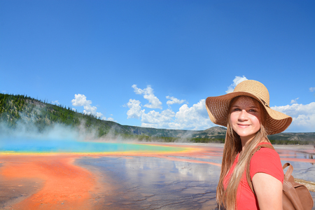 Smiling girl wearing backpack on hiking, sightseeing trip on summer vacation. Grand Prismatic Spring in Yellowstone National Park, Copy space. Wyoming, USA.