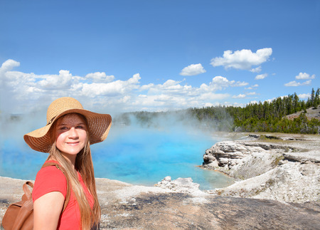 Smiling girl wearing backpack on hiking, sightseeing trip on summer vacation. Excelsior Geyser from the Midway Basin in Yellowstone National Park. Copy space. Wyoming, USA.
