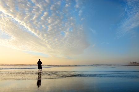 Man walking on beach at sunrise, beautiful cloudy sky reflected on the beach, Buildings, hotels in the background.  Jacksonville, Florida, USA. Stok Fotoğraf