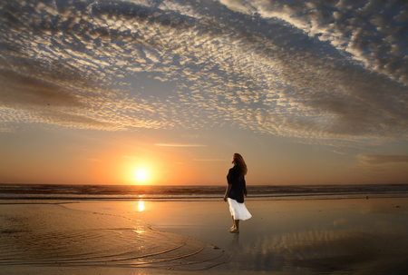Woman  walking  and relaxing on the beautiful beach at sunrise, beautiful cloudy sky and sun  reflected on beach, Jacksonville, Florida, USA. Stok Fotoğraf