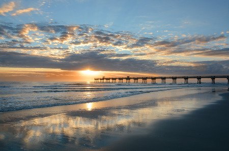 Sun rising over horizon and pier, beach illuminated with sunlight, beautiful sky reflected on the beach. Jacksonville Florida, USA.