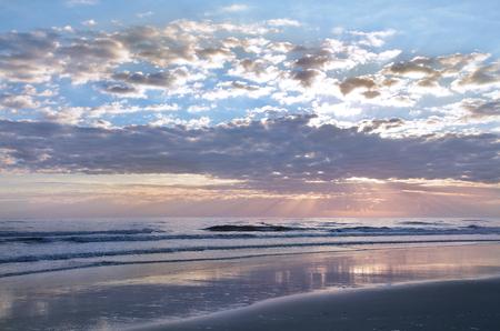 Sun rising over horizon, beach illuminated with sunlight, beautiful sky reflected on the beach. Jacksonville Florida, USA. Stok Fotoğraf