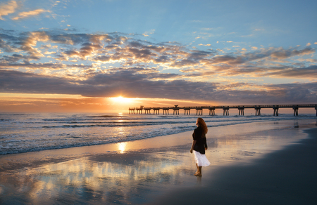 Woman relaxing on the beach at sunrise, beautiful cloudy sky reflected on beach, Jacksonville, Florida, USA.