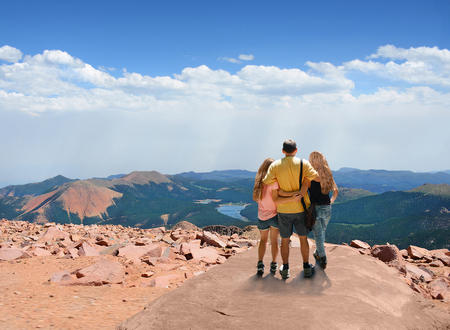 Father with arms around his family looking at beautiful  mountains landscape, on hiking trip, on  top of  mountain rock. View from the top of Pikes Peak.  Pike National Forest, Cascade, Colorado, USA Stok Fotoğraf