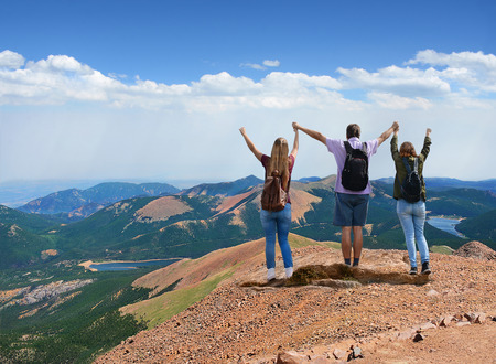 Family hiking trip. Happy people, girls and father with raised hands enjoying time together on top of  beautiful  mountain., view from  top of Pikes Peak.  Pike National Forest, Cascade, Colorado, USA Stok Fotoğraf