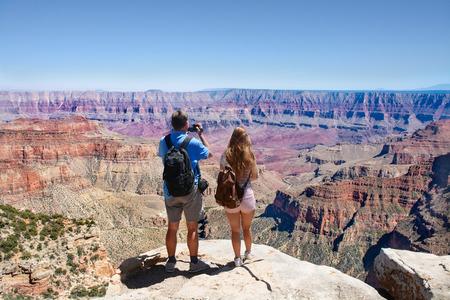 Couple on hiking trip. Man using his camera. Beautiful mountain landscape in Arizona. North Rim, Grand Canyon National Park, Arizona, USA Stok Fotoğraf