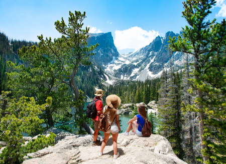 Family standing on top of the mountain enjoying  beautiful scenery. Early summer landscape with lake  and snow covered mountains.  Dream Lake, Rocky Mountains National Park, Colorado, USA.