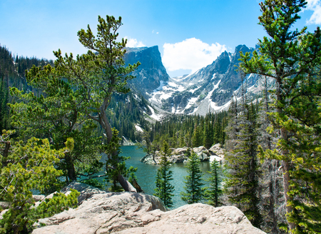 Beautiful lake in the mountains. Early summer landscape with snow covered mountains.  Hallett Peak over the Dream Lake, Rocky Mountains National Park, Colorado, USA.