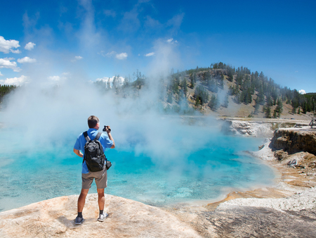 Man relaxing and enjoying beautiful view of gazer on vacation hiking trip. Man filming view of  Excelsior Geyser from the Midway Basin in Yellowstone National Park. Wyoming, USA