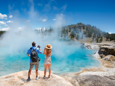 Couple relaxing and enjoying beautiful view of gazer on vacation hiking trip. Man filming view of  Excelsior Geyser from the Midway Basin in Yellowstone National Park. Wyoming, USA Stok Fotoğraf