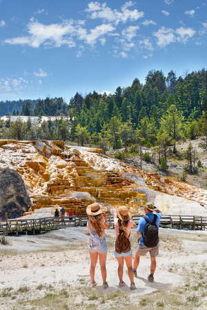 Family on summer hiking vacation. People sightseeing on summer trip. Mammoth Hot Springs on a hill of travertine in Yellowstone National Park. Wyoming,USA.