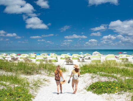 Friends walking on beautiful white sand beach on summer vacation. Girls enjoying time on vacation. Beach umbrellas and chairs green ocean in background.Gulf of Mexico, Clearwater Beach, Florida, USA.