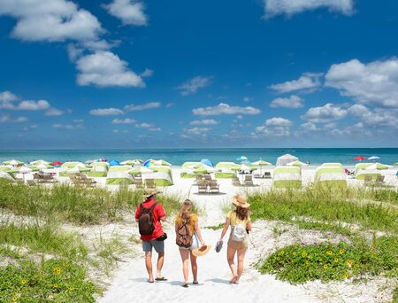 Family walking on beautiful white sand beach on summer vacation in Florida Beach umbrellas and chairs on the beach,  green ocean in background. Gulf of Mexico, Clearwater Beach, Florida, USA.