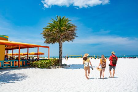 Family walking on beautiful white sand beach on summer vacation in Florida Volleyball nets, beach umbrellas and green ocean in background.  Gulf of Mexico, Clearwater Beach, Florida, USA. Stok Fotoğraf