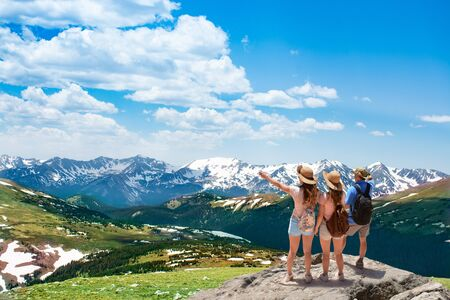 Family standing on top of the mountain looking at beautiful view. Early summer landscape with green meadows and snow covered mountains.  Trail Ridge Road. Rocky Mountains National Park, Colorado, USA. 免版税图像