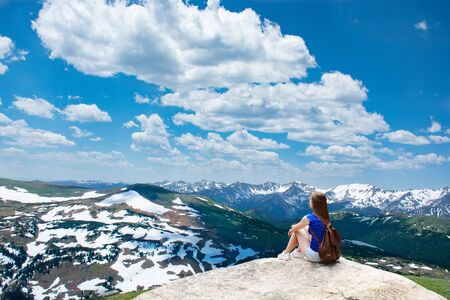 Girl sitting  on the rock on hiking trip in beautiful mountains. Snowy peaks and green meadows and hills View from Trail Ridge Road. Rocky Mountains National Park. Estes, Park,Colorado, USA. Stok Fotoğraf