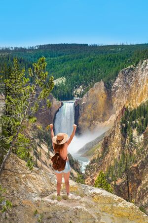 Girl with raised hands relaxing on top of the mountain, looking at beautiful summer  landscape. Woman enjoying time in mountains. Hiking trip. Beautiful Lower Falls at Yellowstone National Park, USA.