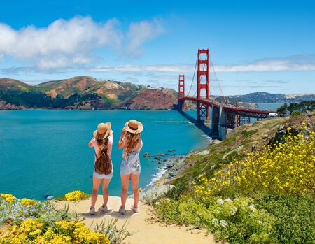 Friends enjoying time together on vacation  trip.  Girls looking at beautiful view of Golden Gate Bridge, over Pacific Ocean. San Francisco, California, USA Stok Fotoğraf