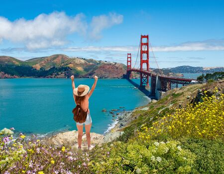 Girl with raised hands relaxing on top of the mountain, enjoying beautiful view. Hiking trip. Golden Gate Bridge, over Pacific Ocean and San Francisco Bay, San Francisco, California, USA Stok Fotoğraf