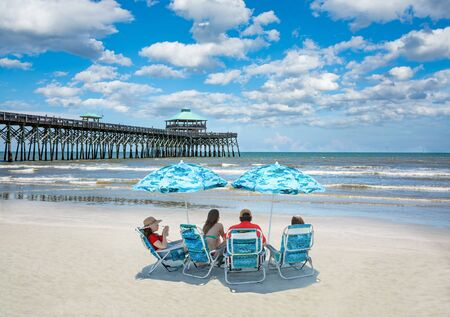 Family relaxing on  the beautiful beach, People enjoying summer vacation by the ocean. Family sitting under beach umbrella.  Cloudy sky and pier in the background. Folly Beach, South Carolina USA.