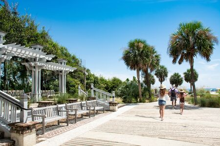 Family walking to the beach on summer vacation. People enjoying summer vacation by the ocean. Palm trees on the pathway leading to ocean. Coligny Beach Park, Hilton Head Island, South Carolina, USA Stok Fotoğraf