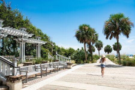 Girl walking to the beach on summer trip. Woman enjoying vacation alone.. Coligny Beach Park, Hilton Head Island, South Carolina, USA