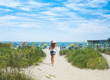 Girl walking on the beach on summer vacation.  Beach chairs and parasols on sand in the background.  Myrtle Beach, South Carolina, USA. Stok Fotoğraf