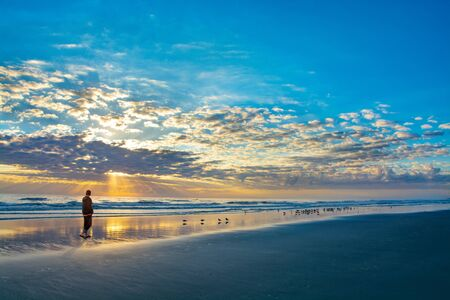 Man walking on beach at sunrise, beautiful cloudy sky reflected on the beach, Man relaxing on summer vacation.  Beautiful cloudy sky reflected in the water. Jacksonville, Florida, USA.
