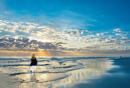 Girl walking on beach at sunrise, enjoying beautiful scenery. Beautiful cloudy sky and sun reflected on the beach. Woman relaxing on summer  vacation.  Jacksonville, Florida, USA.