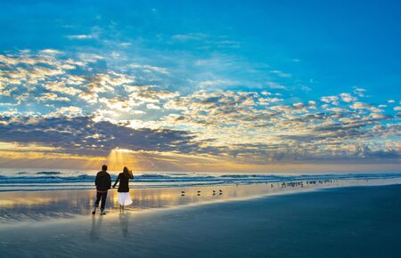 Couple walking on beach at sunrise, enjoying time together. Beautiful cloudy sky and sun reflected on the beach, People relaxing on summer  vacation.  Jacksonville, Florida, USA. 版權商用圖片