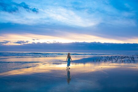 Girl walking on the beautiful beach at sunrise, sun and clouds reflected in the water on the beach. Woman enjoying time on summer vacation.  Daytona, Florida, USA.