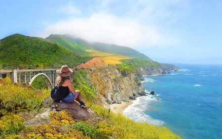 Woman on hiking trip looking at beautiful summer mountains, coastal landscape, Bixby Bridge,  famous bridge on highway 1 in California over Pacific Ocean. Big Sur, California, USA